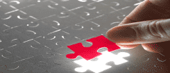 image of red puzzle piece being inserted into a grey puzzle