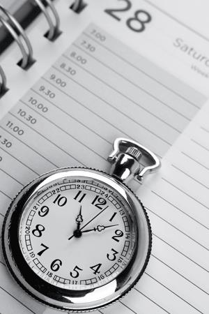 Image of a pocket watch on a calendar